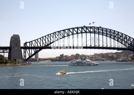 Harbour Bridge with cruise catamaran ship and water taxi boat in Sydney New South Wales NSW Australia - Stock Photo