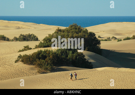 Hikers walking in the sand dunes of Maspalomas beach, in the south coast of Gran Canaria island one of Spain's Canary - Stock Photo