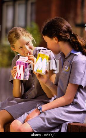 Young girls drinking flavoured milk Melbourne Victoria Australia vertical  - Stock Photo