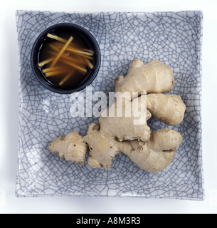 a piece of ginger on a plate with a bowl of preserved ginger - Stock Photo