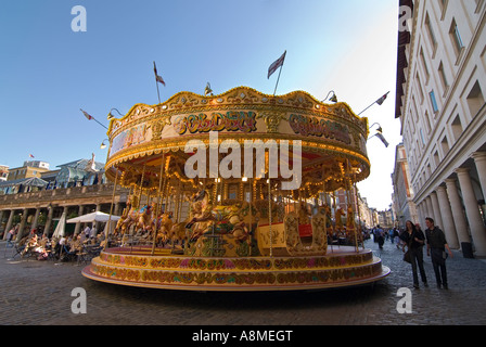 Horizontal close up of a bright fairground carousel in the middle of Covent Garden on a bright sunny evening. - Stock Photo