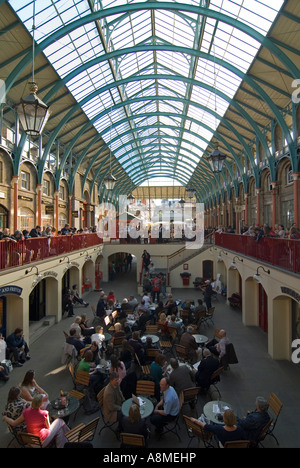 Vertical close up of people being entertained by street performers inside the 'Apple Market' at Covent Garden. - Stock Photo