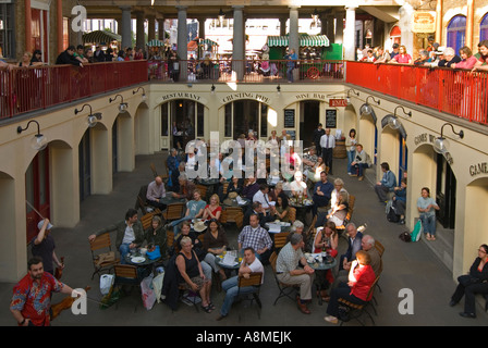 Horizontal close up of people being entertained by street performers inside Covent Garden market on a sunny day - Stock Photo