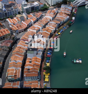 Aerial view down on Boat Quay on Singapore River with shops restaurants boats moored Elgin Bridge in background - Stock Photo