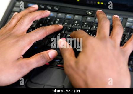Teacher writing on a laptop computer keyboard. After School Study Program. St Paul Minnesota USA - Stock Photo