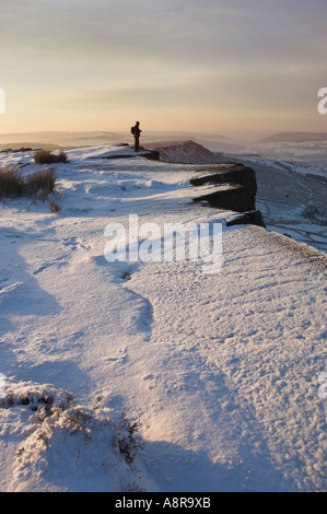 Hiker in the snow early morning on Froggatt edge Derbyshire Peak District National park Calver England UK GB EU - Stock Photo