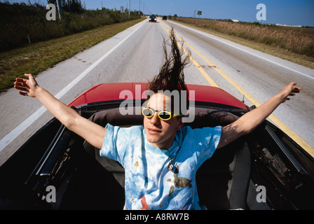 Young teenage girl in the back of a convertible car with the top down and her hair blowing in the wind - Stock Photo