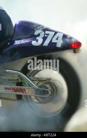 Smoke from burning rubber tyre of 1300 cc Suzuki Hayabusa motor bike preparing to run at Brighton Speed Trials Madeira - Stock Photo