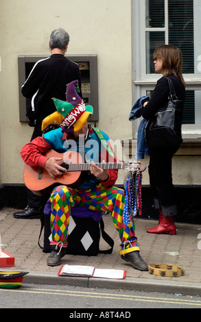 Busker on pavement outside the HSBC Bank ATM cash machine on high street in Hay on Wye Powys Wales UK - Stock Photo