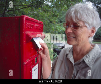 elderly woman posting a letter in traditional red British letter box in the country - Stock Photo