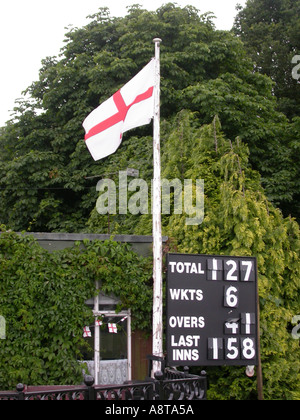 Flag of Saint George and cricket scoreboard West End village green Esher; patriotic symbols of England and the English - Stock Photo