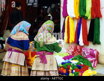 Two Flower Hmong women looking at brightly coloured wools at the Sunday market, Bac Ha, NW Viet Nam - Stock Photo