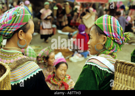 Two Flower Hmong women in colourful traditional clothing talking at the Sunday market, Bac Ha, NW Viet Nam - Stock Photo