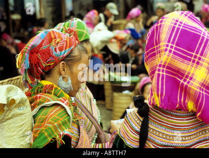 Two Flower Hmong women in colourful traditional clothing at the Sunday market, Bac Ha, NW Viet Nam - Stock Photo
