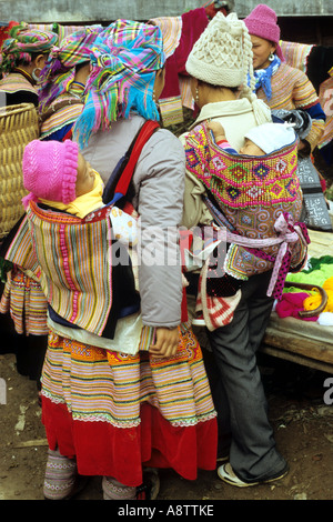 Flower Hmong women in traditional and modern dress, with babies in back carriers, Sunday market, Bac Ha, NW Viet - Stock Photo