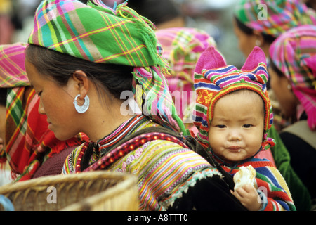 Traditionally dressed Flower Hmong woman with baby in a back carrier, Sunday market, Bac Ha, NW Viet Nam - Stock Photo