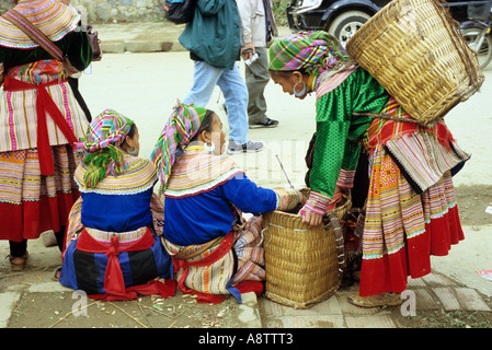 Four traditionally dressed Flower Hmong women at the roadside, Sunday market, Bac Ha, NW Viet Nam - Stock Photo