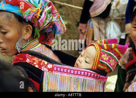 Traditionally dressed Flower Hmong woman with baby in a back carrier, Saturday market, Can Cau, NW Viet Nam - Stock Photo