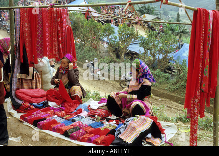 Display of brightly coloured velvet fabric for sale at a stall, at the Saturday market, Can Cau, NW Viet Nam - Stock Photo
