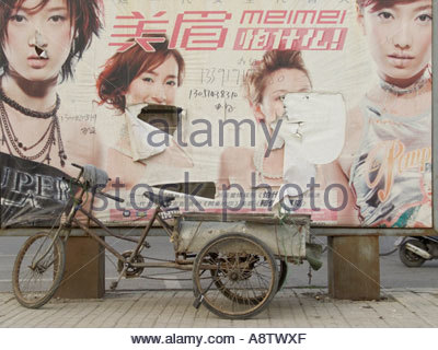a dilapidated advertising billboard with an bicycle cart parked in front of it Beijing China - Stock Photo