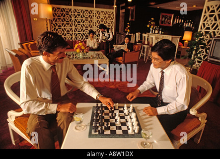 Two men sitting indoors playing a game of chess in hotel lounge.