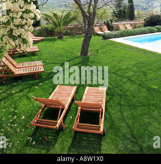 Luxury wooden sunbeds next to a swimming pool in beautiful green Spanish garden on a sunny day - Stock Photo