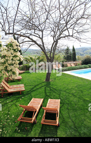 Wooden sunbeds next to a swimming pool in beautiful green Spanish garden on a sunny day - Stock Photo