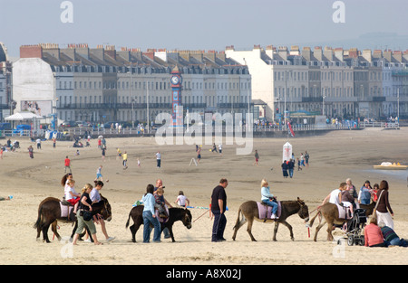 Donkey rides on the beach, looking toward seafront hotels and guest houses, at Weymouth Dorset Southern England UK Stock Photo