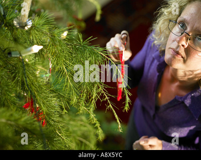young woman dressing the christmas tree with a silver star ...