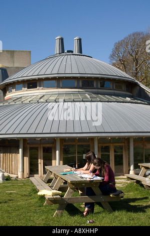 Two women students working studying in the sunshine outside Aberystwyth arts centre building sunny afternoon in - Stock Photo