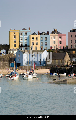pastel coloured painted georgian town houses overlooking the sandy beach and boats in the harbour at Tenby wales - Stock Photo