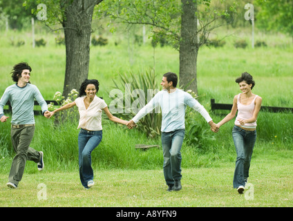 Four young friends holding hands and skipping in field - Stock Photo
