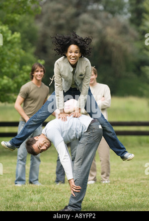 Young woman playing leapfrog with young man while friends look on - Stock Photo