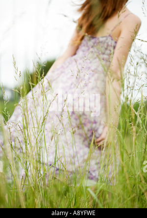 Young woman walking through grass, dress blowing in wind - Stock Photo