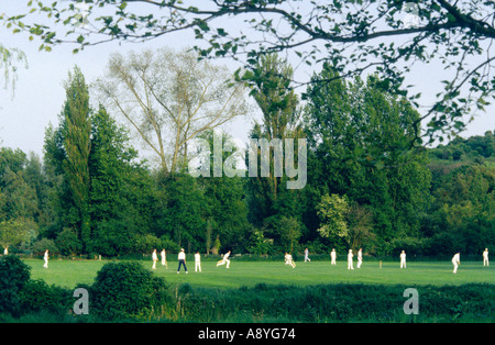 Local cricket teams play in riverside meadow in the town of Winchester, Hampshire, England, UK. - Stock Photo