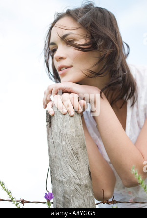 Young woman leaning on wooden post - Stock Photo