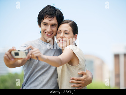 Young couple taking picture of themselves together - Stock Photo
