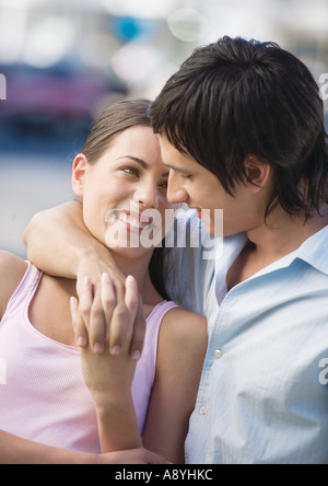 Young couple embracing, holding hands and smiling at each other - Stock Photo