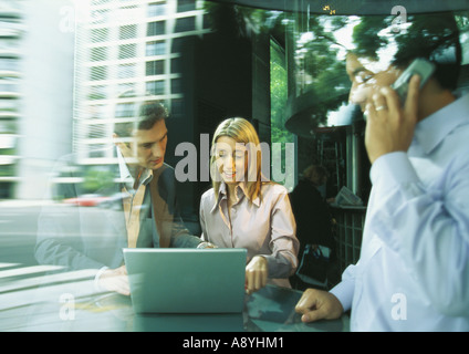 Businessman and businesswoman using laptop while second man uses cell phone - Stock Photo