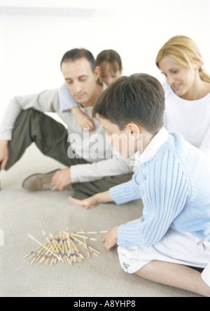 Family playing pick-up-sticks on floor - Stock Photo