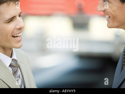 Two businessmen face to face, smiling - Stock Photo