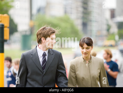 Young businessman walking with female collegue - Stock Photo