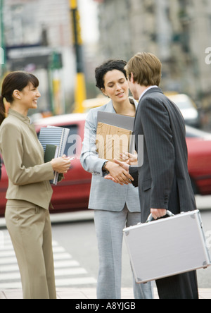 Business people shaking hands on side of street - Stock Photo