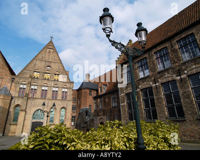Old monastery buildings in the historic city center of Brugge Bruges Belgium with bronze statue of two hugging monks - Stock Photo
