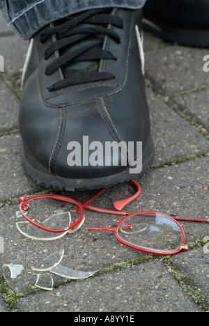 boy steps on eyeglasses - Stock Photo