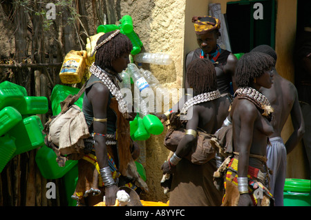Black skinned Hamar people with white kauri mussel necklesses in front of green plastic canisters market of Dimeka - Stock Photo