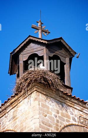 Stork on nest, Holy Trinity Church, Sveta Troitsa Church, clock and bell tower, Bansko, Bulgaria - Stock Photo