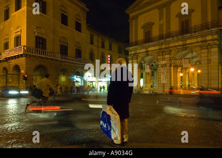 Horizontal wide angle of an old man carrying lots of plastic bags trying to cross a busy road at night. - Stock Photo