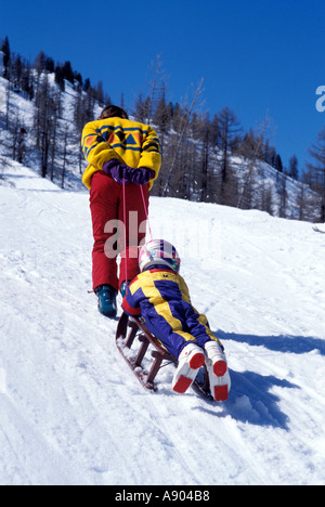 Woman pulling young child on a toboggan up the hill - Stock Photo