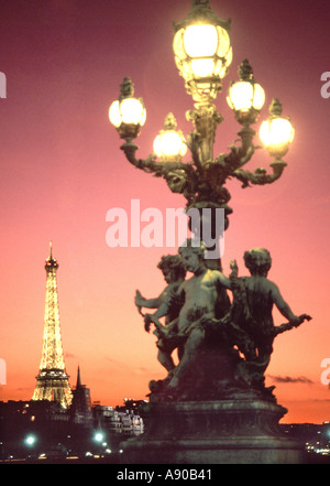 Close up of Cherub statue sculpture on lamppost on Pont Alexandre III 3rd bridge ornate lamp cluster natural sunset - Stock Photo